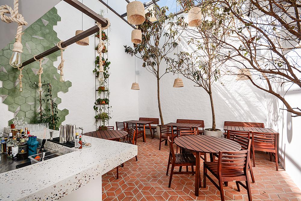 Ambiente do Casa Rios. Mesas e cadeiras de madeira espalhadas em um salão de paredes brancas e iluminado por luz natural.