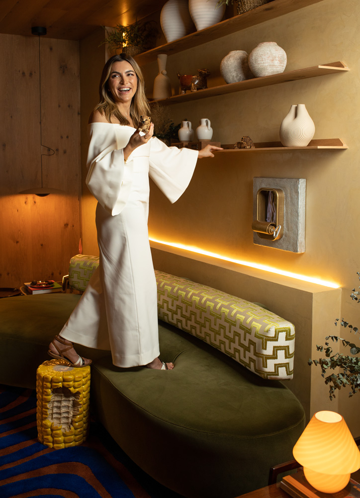 A imagem mostra Ana Weege, em pé em cima de um sofá verde, com a mão apoiada sobre uma das pratilheiras do ambiente.