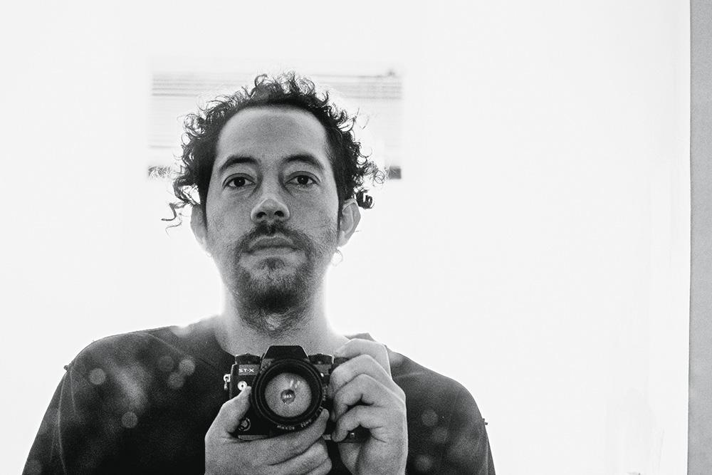foto em preto e branco de renato custódio capturando a si mesmo com sua câmera fotográfica