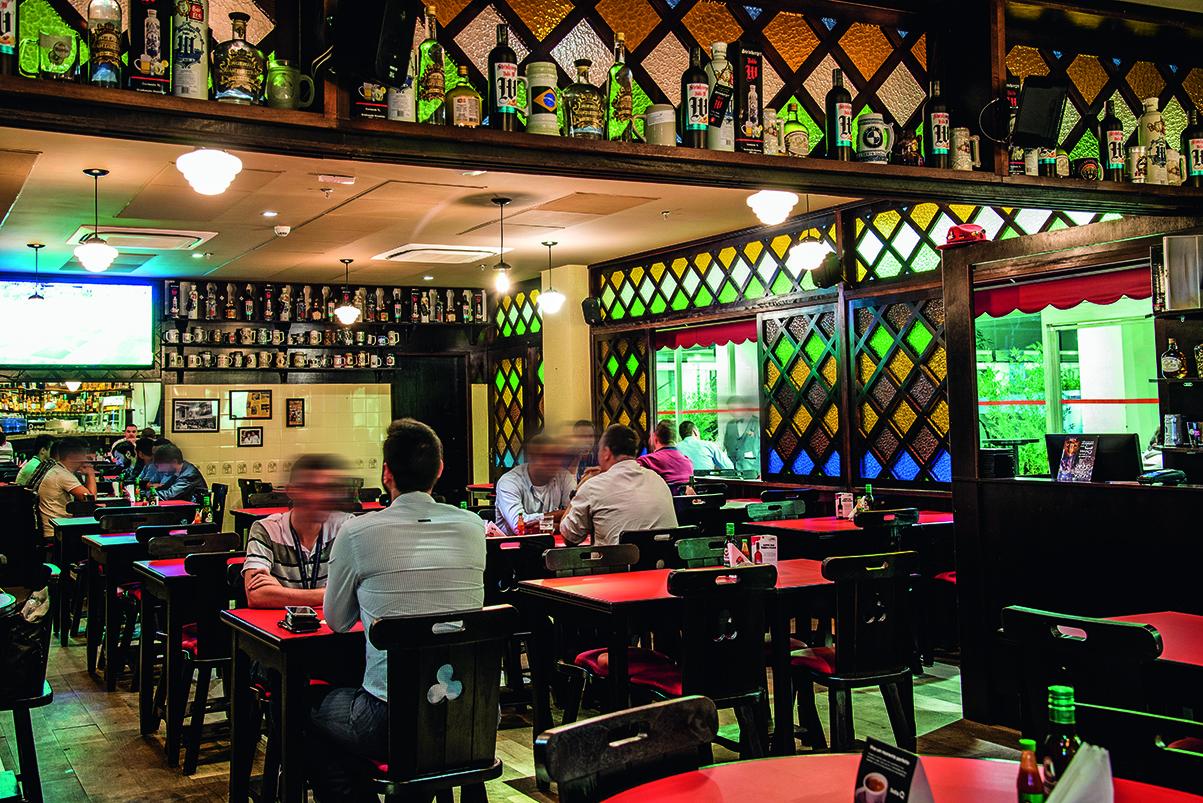 Ambiente do Bar Léo decorado por mosaicos de vidro e garrafas à vista