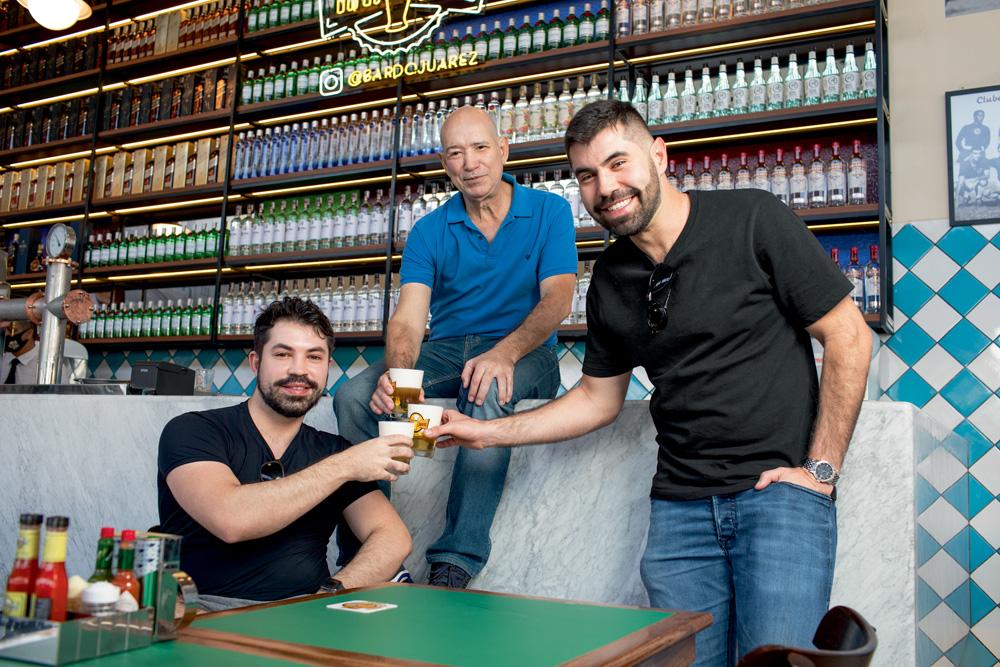 A imagem mostra Joarez, sentado no balcão do bar, e seus dos filhos ao lado, um sentado em uma cadeira e outro de pé, brindando copos cheios de chopp.