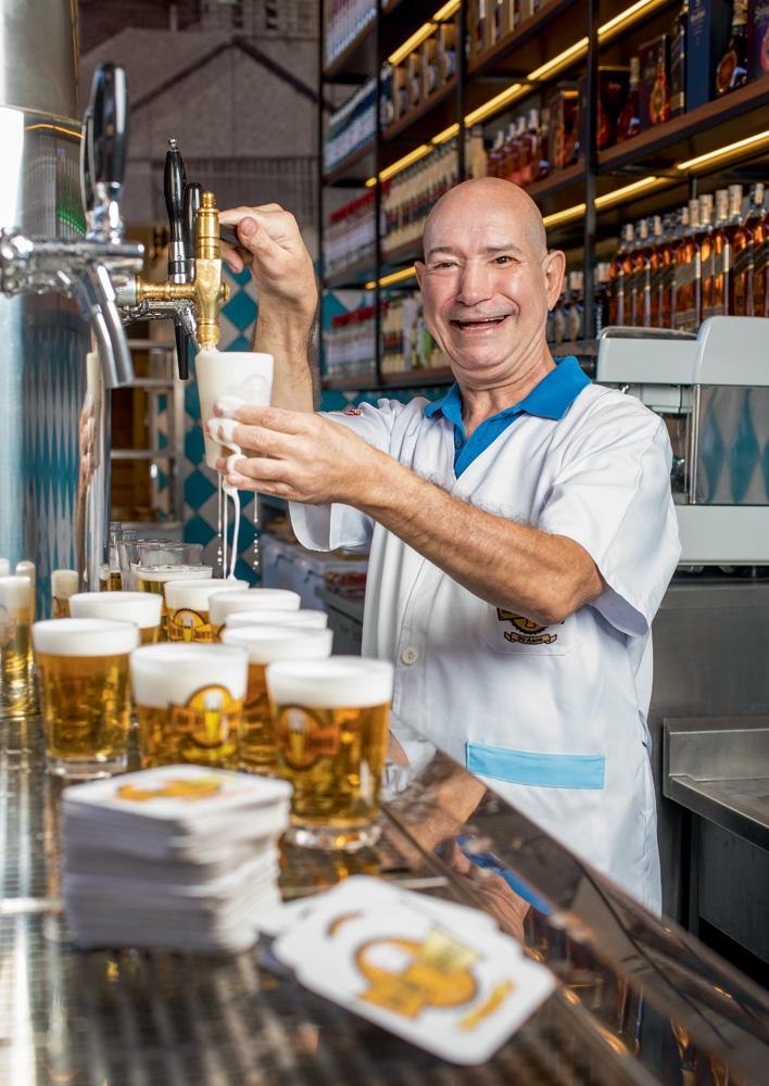 A imagem mostra Joarez enchendo um copo em uma chopeira enquanto o líquido da bebida escorre para fora do objeto. Ele está de avental e sorrindo.