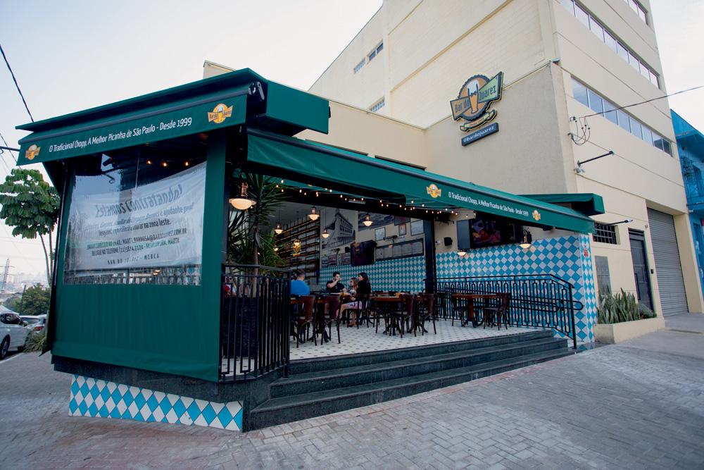 A imagem mostra mostra o bar do Juarez em uma esquina, com o toldo aberto para a rua.