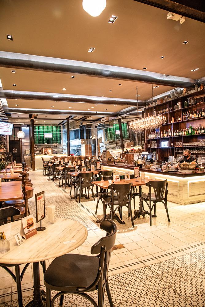 Ambiente do bar, bastante iluminado, decorado por lustres. Mesas de mármore e de madeira à vista, junto de cadeiras de madeira.