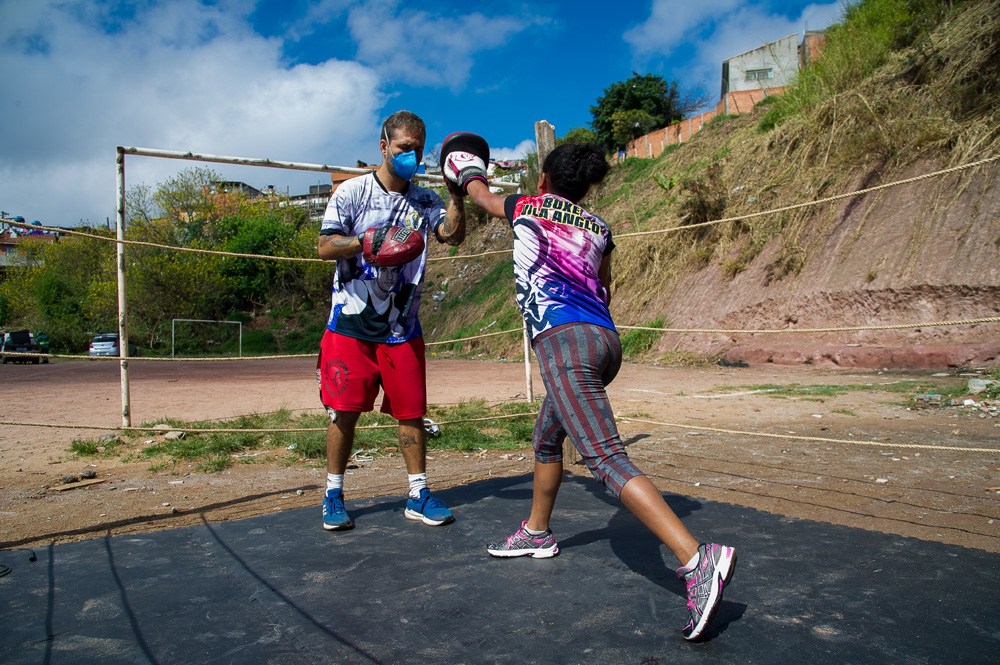A imagem mostra um homem, de máscara, com uma luva de treino de boxe recebendo um soco justamente dela por uma criança, jovem. Eles estão em um ringue improvisado e ambos de máscara.