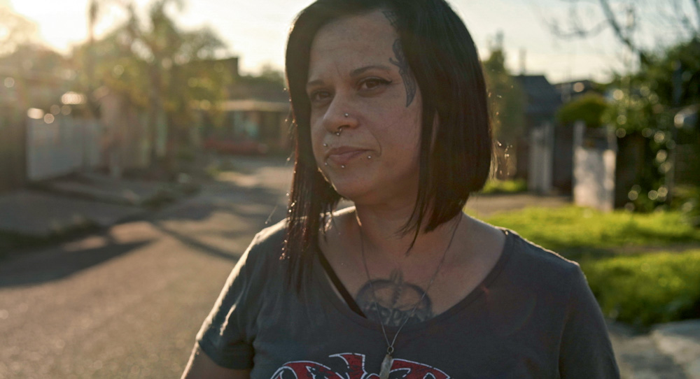 Uma mulher de cabelo chanel preto olha para o horizonte. Tem algumas tatuagens, uma no peito e outra ro rosto
