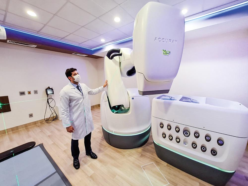 A imagem mostra uma grande máquina branca de uns 3 metros conhecida como Cyberknife.