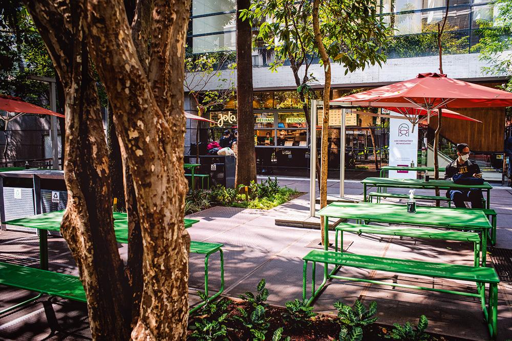 Praça na lateral do Shopping Cidade São Paulo com mesas metálicas de cor verde e guarda-sóis de cor vermelha em meio à pequenas árvores de jabuticaba