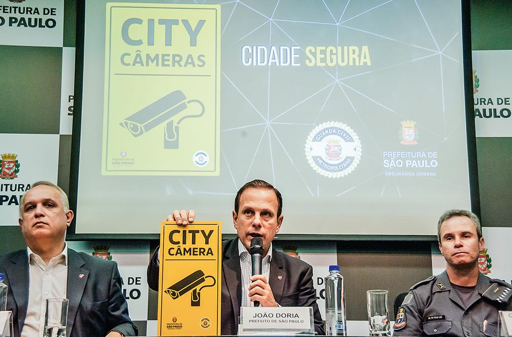 joão doria sentado discursando fazendo anúncio do City câmeras, segurando placa do projeto e com slide projetado atrás dele