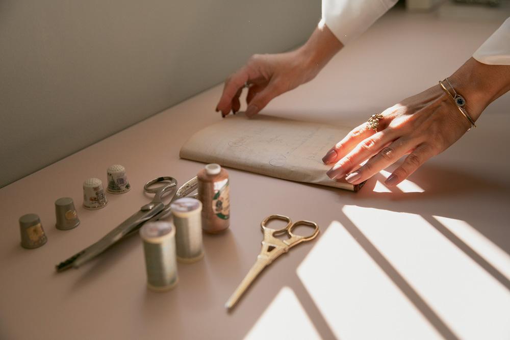 close de mãos de Eduarda Galvani trabalhando em vestidos, com ferramentas de costura ao lado