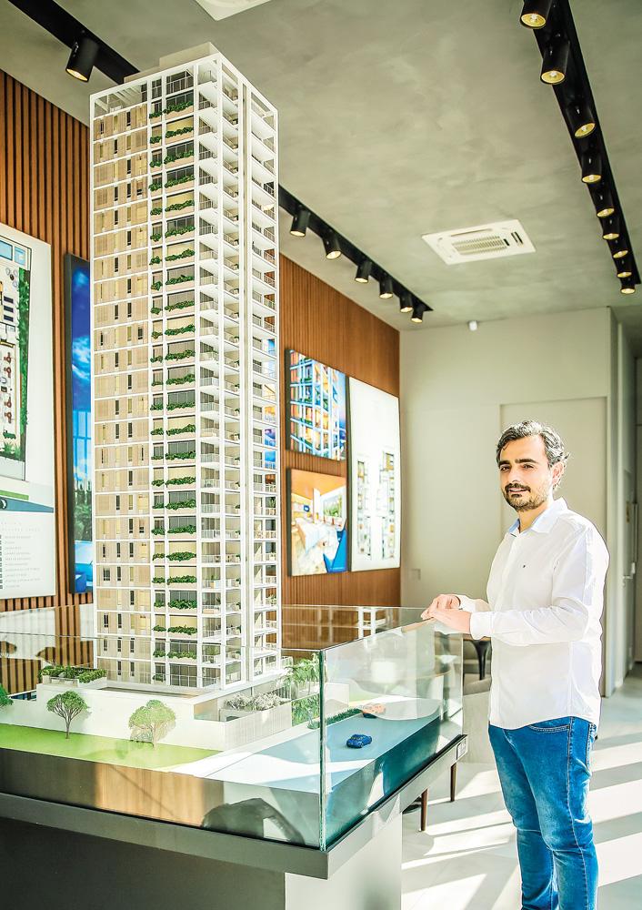 Um homem de camisa social posa ao lado de uma maquete de um prédio de luxo em uma sala comercial
