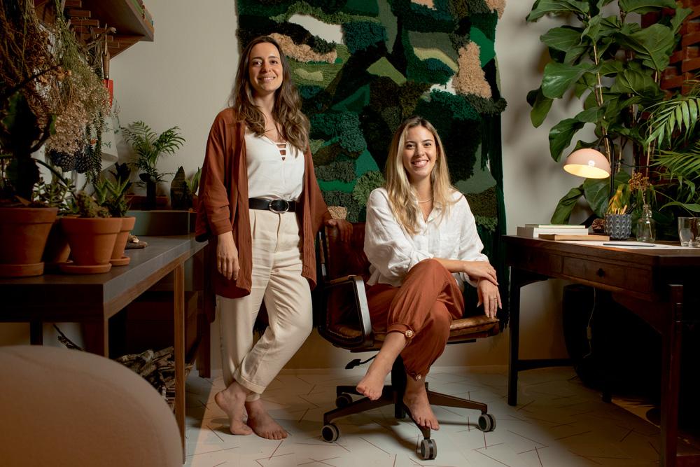 A imagem mostra Fabiana Silveira e Patricia De Palma, a primeira sentada e a segunda em pé, sorrindo para a câmera em seu ambiente.
