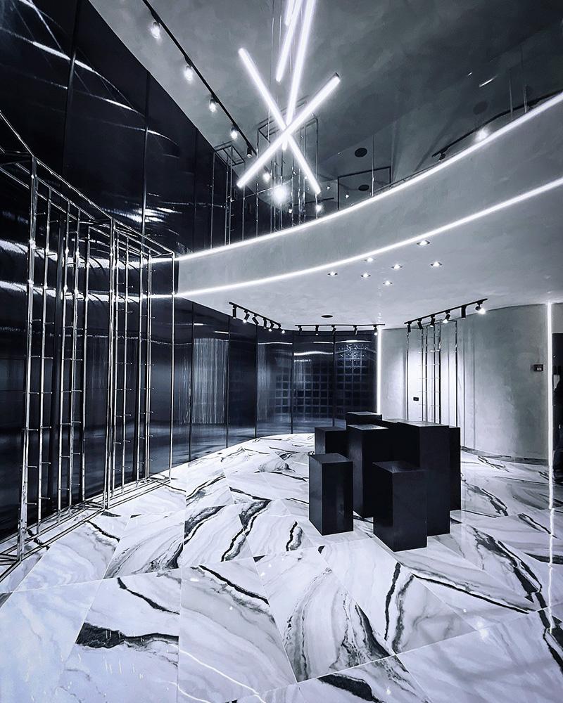 Um espaço de uma loja. A decoração é toda em azul bem escuro e branco. Há algumas colunas pretas no centro do espaço, que é bem moderno, mas não está com roupas nem cabides etc