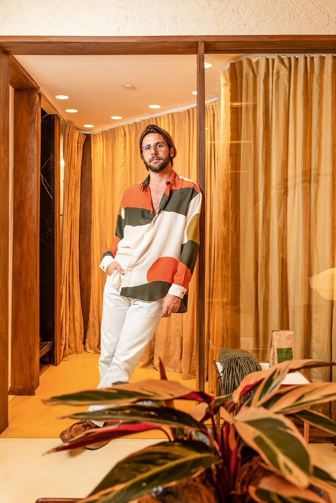 Um homem vestido de camisa e calça branca, com detalhes em verde e laranja, posa no provador de uma grife no shopping