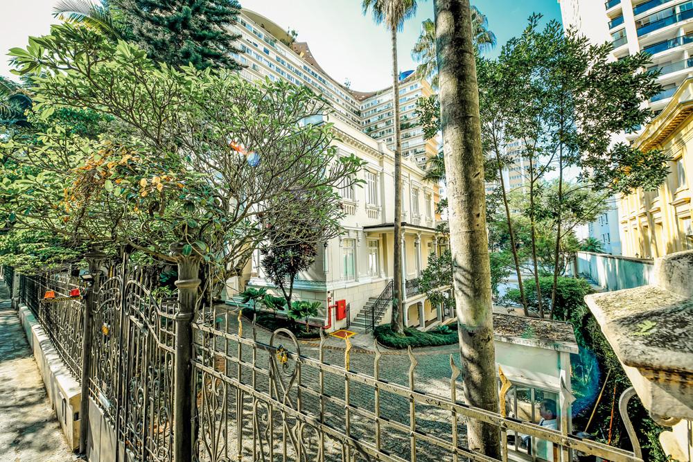 Foto lateral do casarão da Mitra Arquidiocesana de São Paulo, no Higienópolis. Há árvores cercando a construção