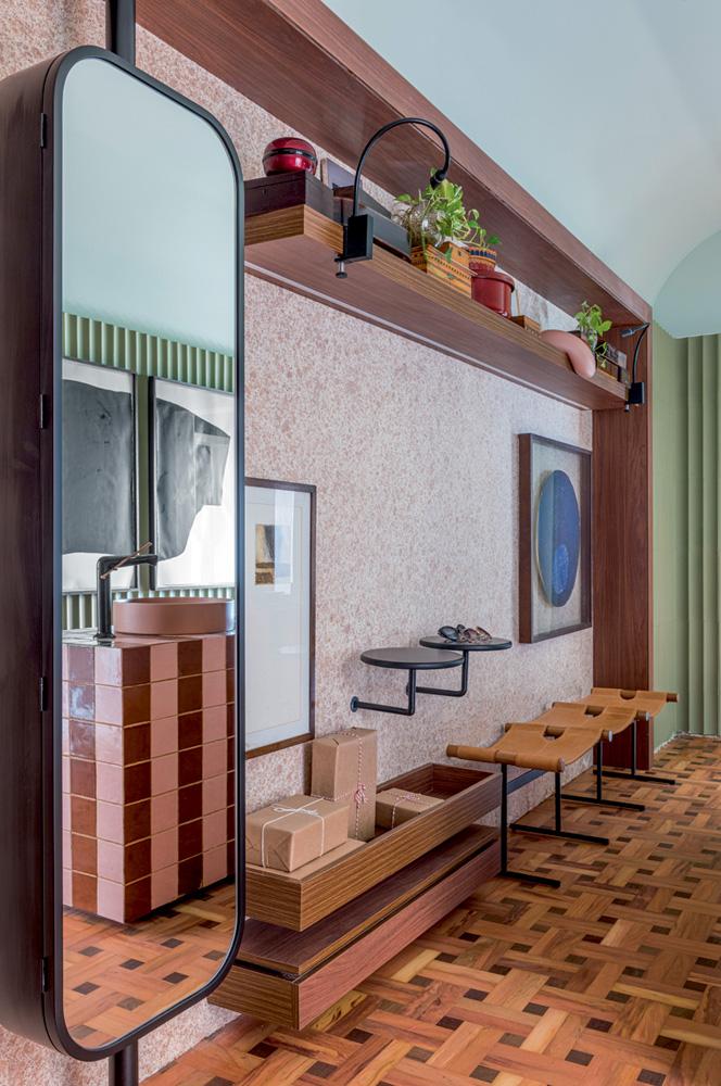 A imagem mostra o hall, com espelho e pequenas cadeiras ao fundo.
