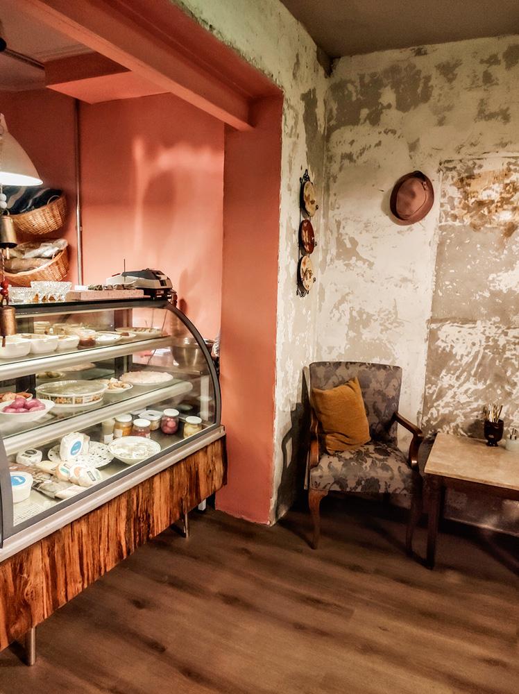 Vitrine de petiscos e comidinhas presente no interior do ambiente do Augustín Bar à esquerda e poltrona com mesinha à direita