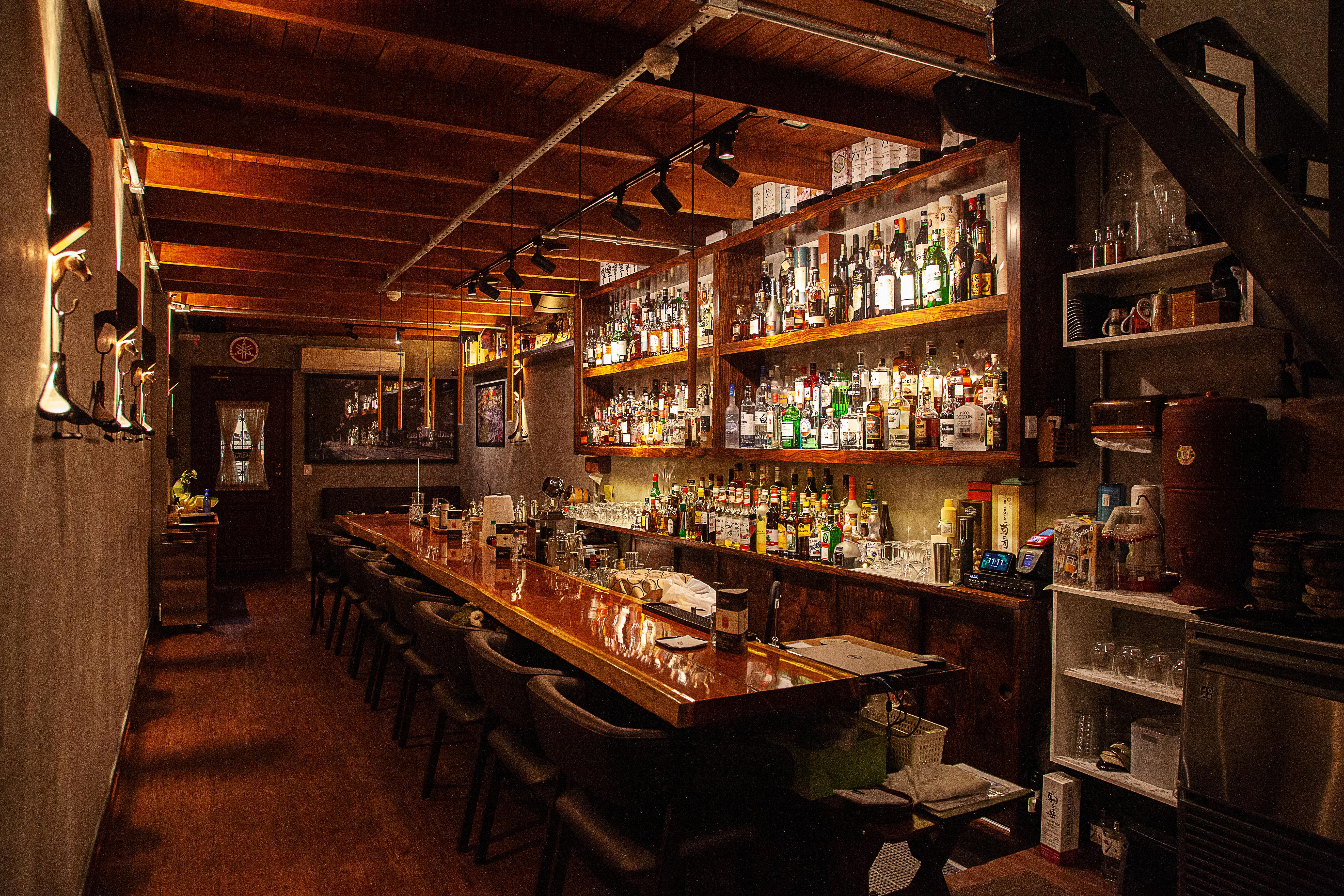 Salão do The Punch Bar, com balcão de madeira em frente à estante com garrafas de bebida.
