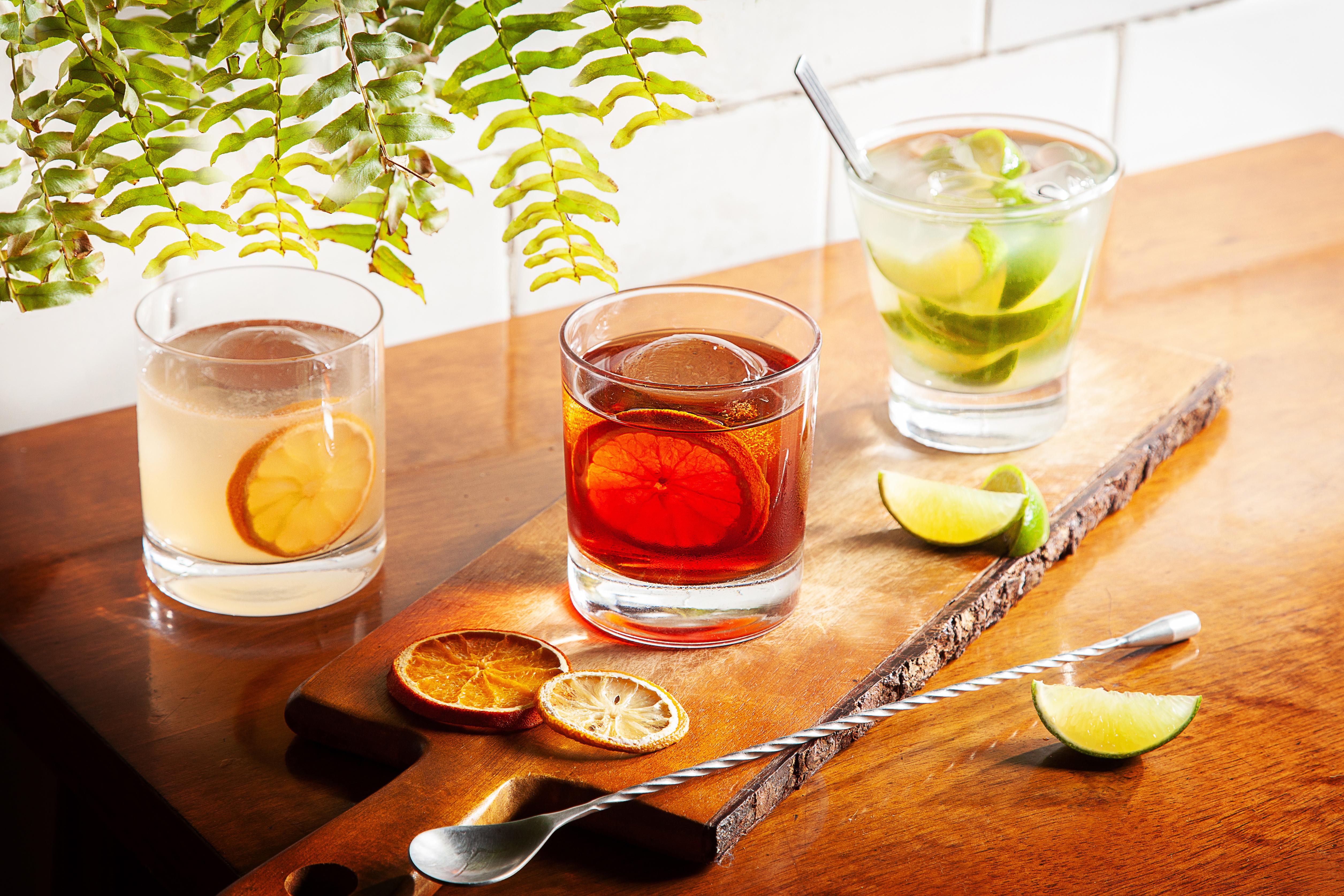 Três copos de drinques, um boulevardier, uma caipirinha e um fitzgerald sobre tábua em cima de mesa de madeira.