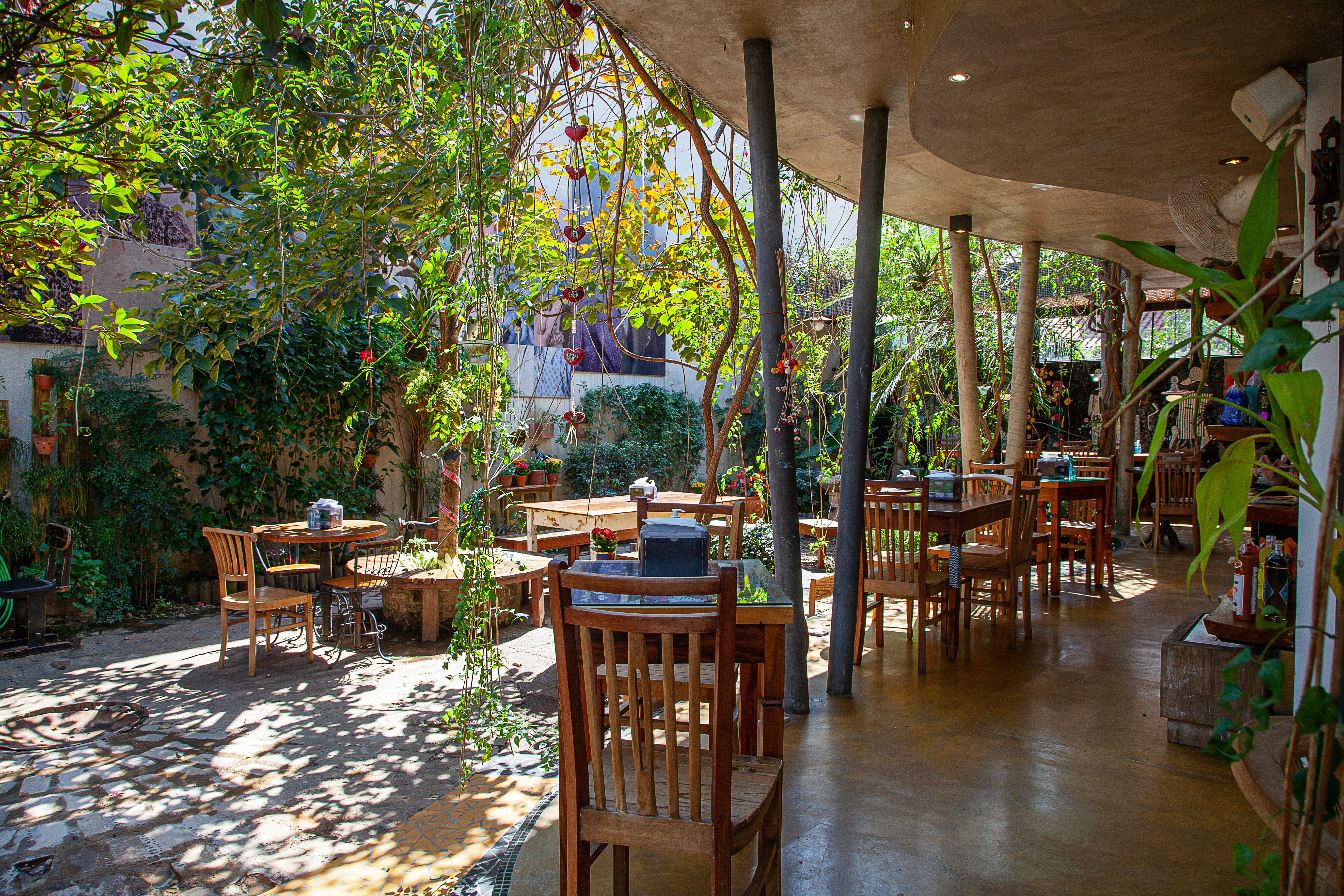 Mesas de madeira dispostas em salão avarandado do restaurante Gansara.l