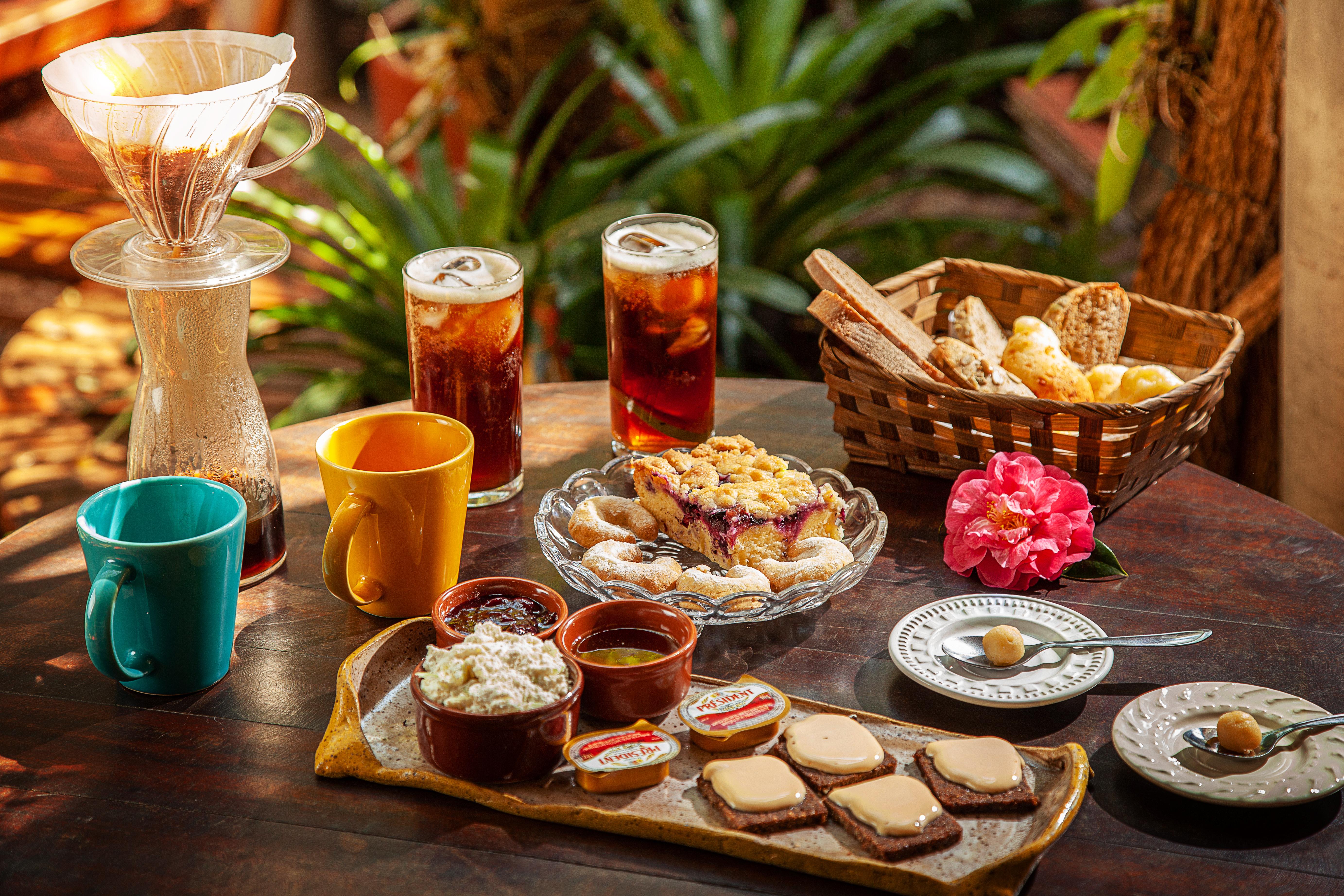 Itens de café da manhã dispostos sobre mesa de madeira.