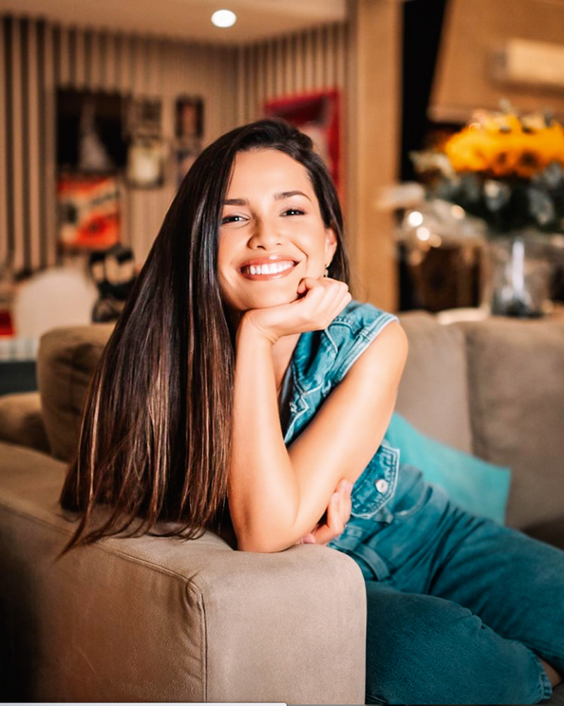 A imagem mostra Juliette sentada em um sofá, com a mão no queiro e sorrindo para a câmera.