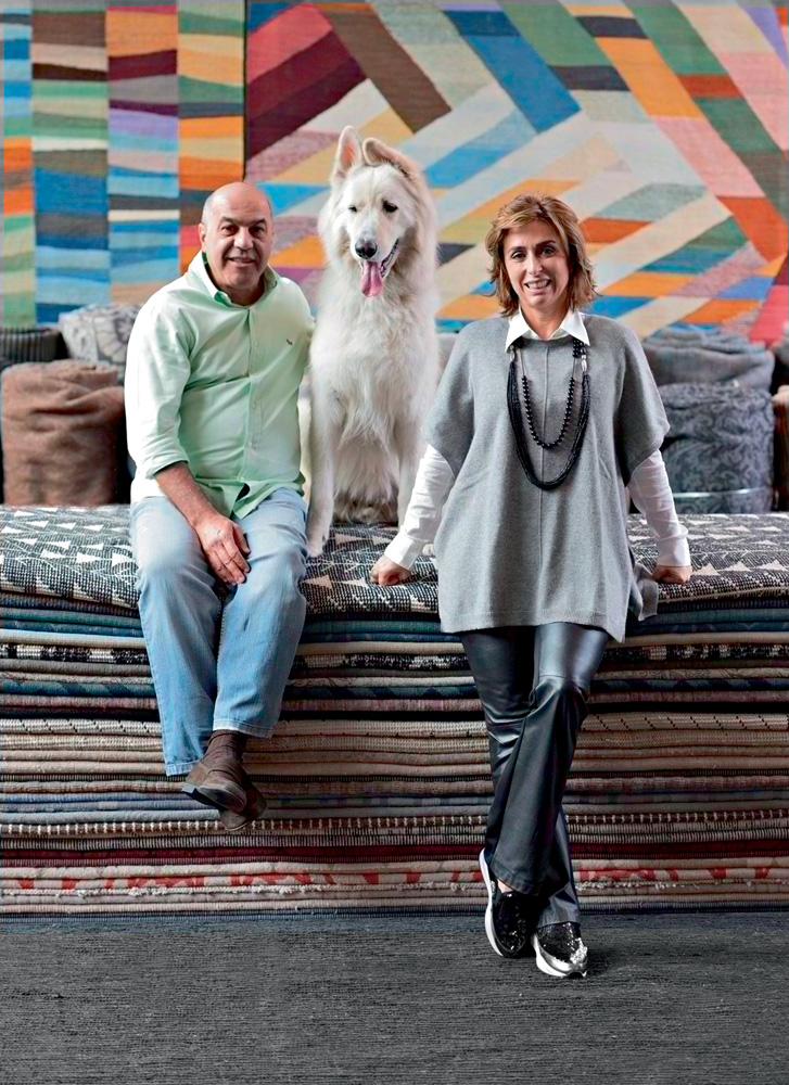Kamyar Abrarpour e Francesca Alzati posando para foto junto com um cachorro e tapetes da loja, empilhados. kamyar está junto com o cachorro sentado nos tapetes e francesca está apoiado nos tapetes, ao lado de kamyar e o cão