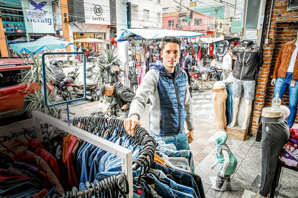 A imagem mostra Pimenta, com uma mão sob uma estrutura de cabides de roupa e olhando para a câmera na Rua Oriente.
