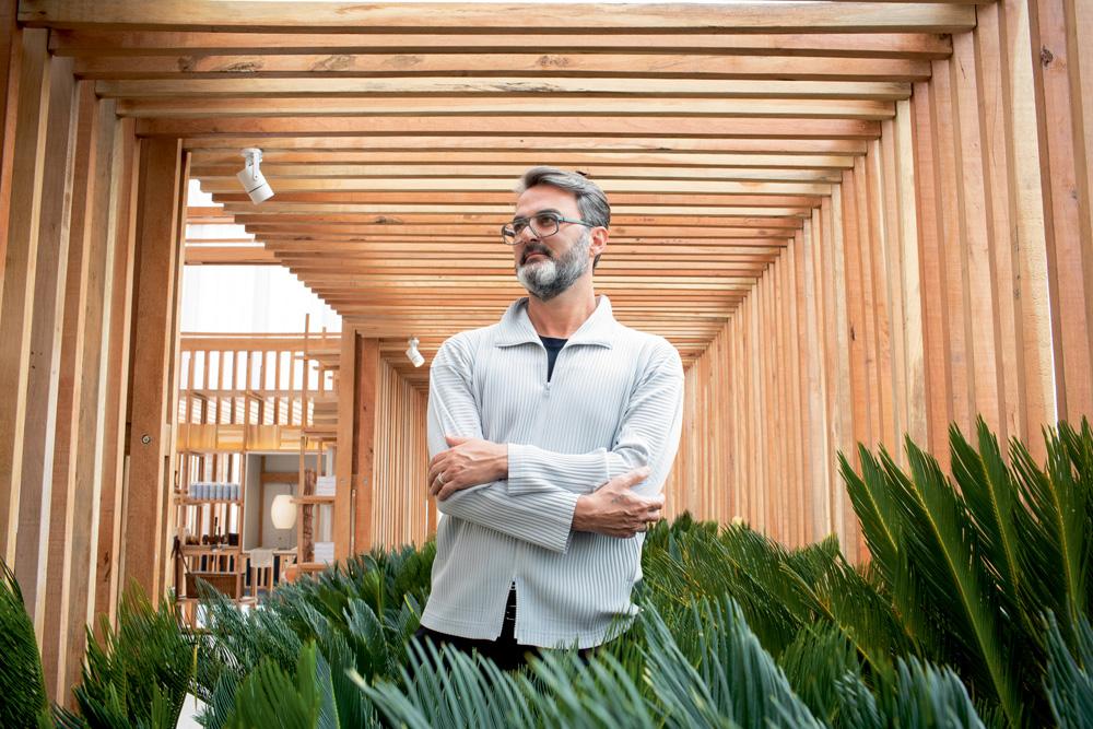 A imagem mostra Leo Romano de braços cruzados em um ambiente com estrutura de madeira.