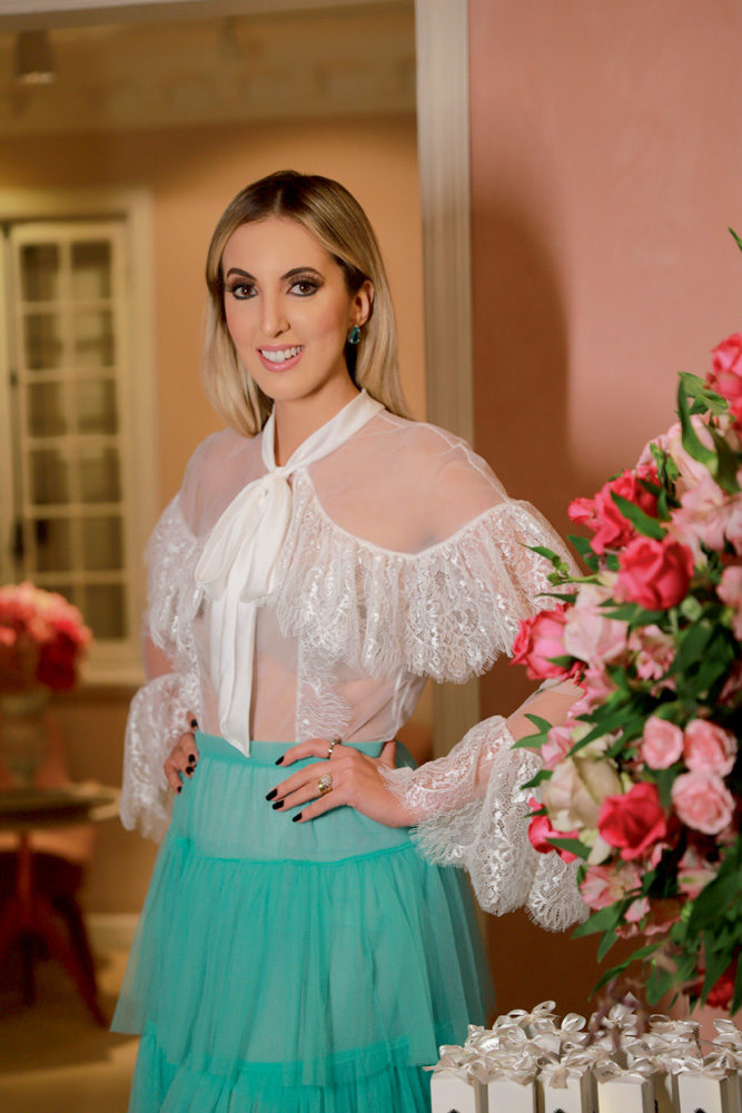 Estilista Letícia Manzan sorrindo para foto com vestido de duas cores, branco e turquesa