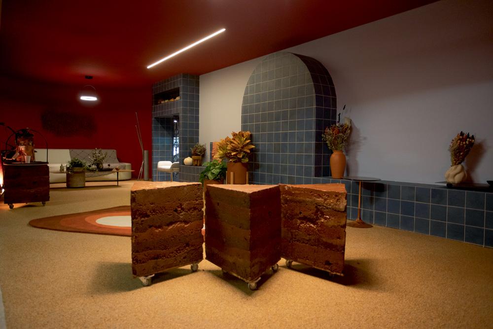 A imagem mostra uma sala com três cadeiras em forma de pedaços de bolo de chocolate.