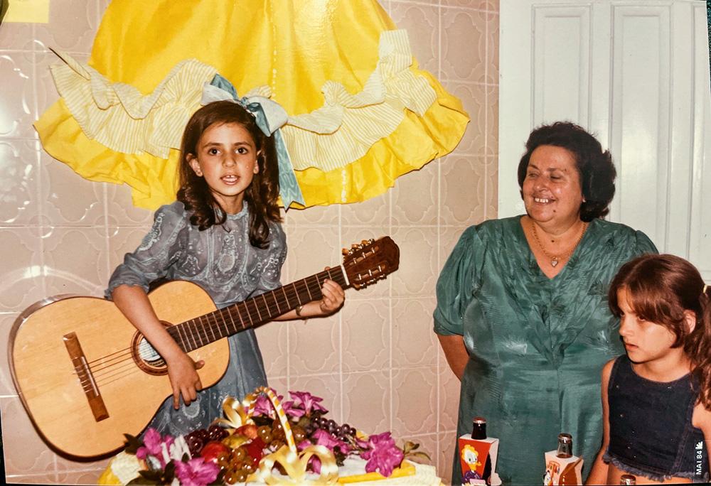 A imagem mostra Ludmilla com 7 anos, em seu aniversário, tocando violão enquanto é observada pela avó.
