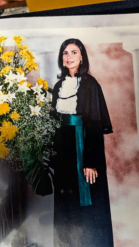 A imagem mostra Ludhmilla, com roupa de formatura, ao lado de flores.