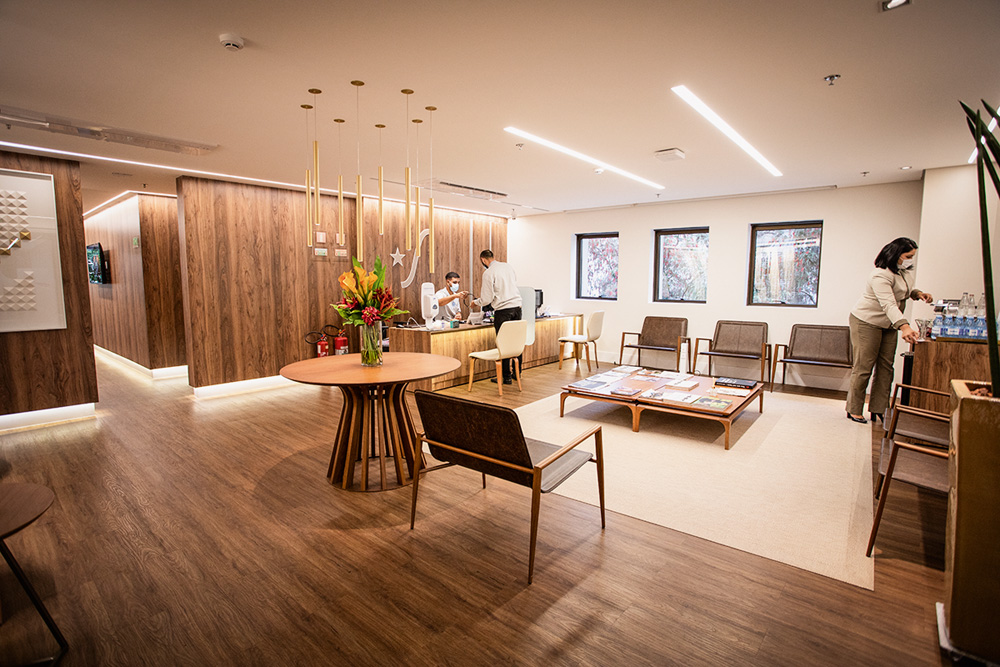 A imagem mostra um sala de espera larga. Há algumas cadeiras e a decoração é majoritariamente de madeira. Há duas pessoas na imagem, distantes, usando máscara.