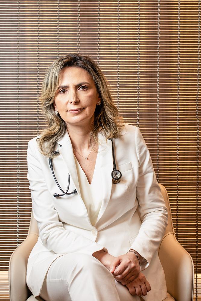 Retrato da cardiologista Dra. Ludhmila Hajjar em seu consultório, na Vila Olímpia. Ela está de jaleco branco, com um estetoscópio nos ombros.