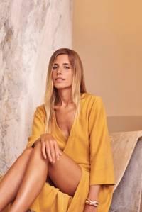 Marcella Franklin posa de pernas encolhidas, sentada, com uma das mãos no joelho. Veste um vestido na cor amarela, quase mostarda, e tem cabelos lisos loiros.