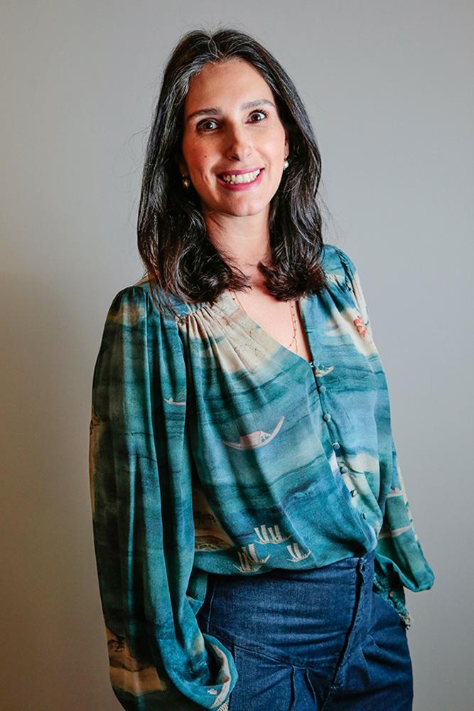 Maria Fernanda Quartiero sorrindo em estúdio. ela está utilizando uma blusa azul