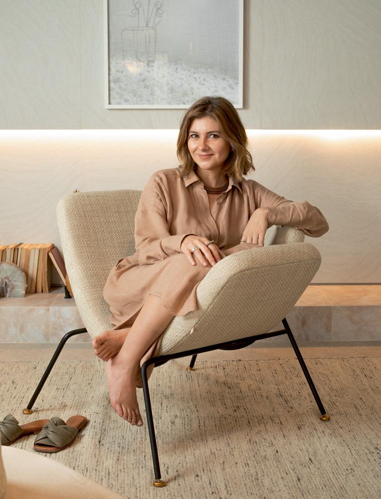 A imagem mostra Melina sentada em um assento em forma de U acolchoado.