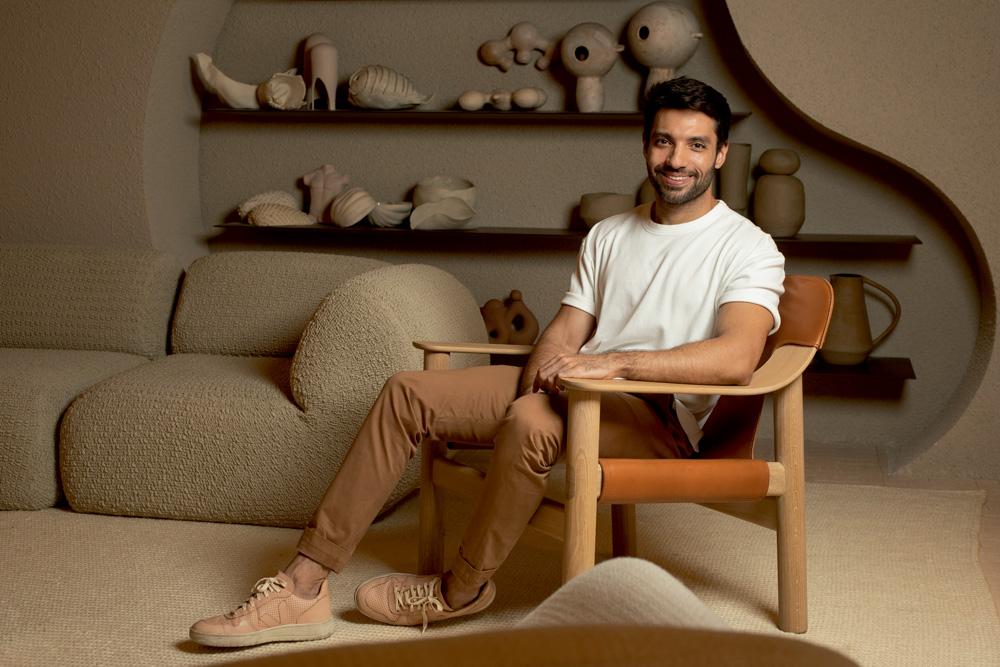 A imagem mostra Nildo sentado em uma poltrona. Ao fundo, peças de cerâmica de seu ambiente.