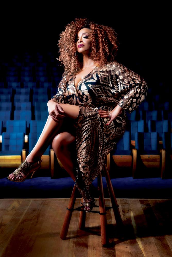 Paula Lima posa de pernas cruzadas em banquinho, com cadeiras de teatro ao fundo, todas na cor azul.