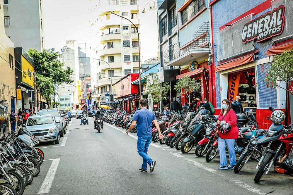 A imagem mostra a rua General Osório. Estreita, há muitas motos estacionadas no lado direito da imagem e um homem atravessando a rua.