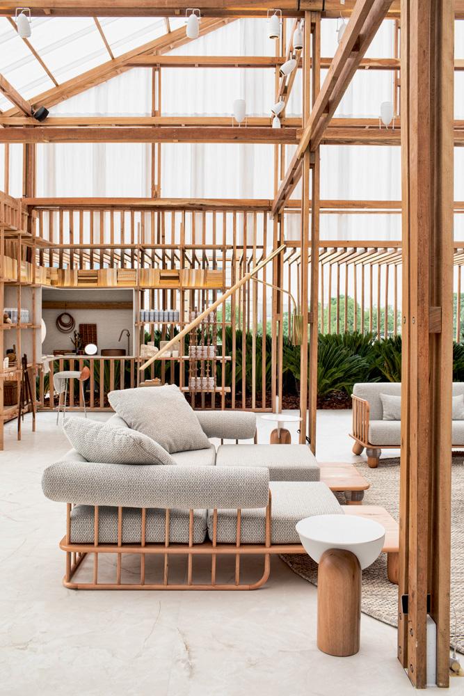 A imagem mostra uma sala com sofás e estruturada majoritariamente com madeiras, como em seus corrimões.