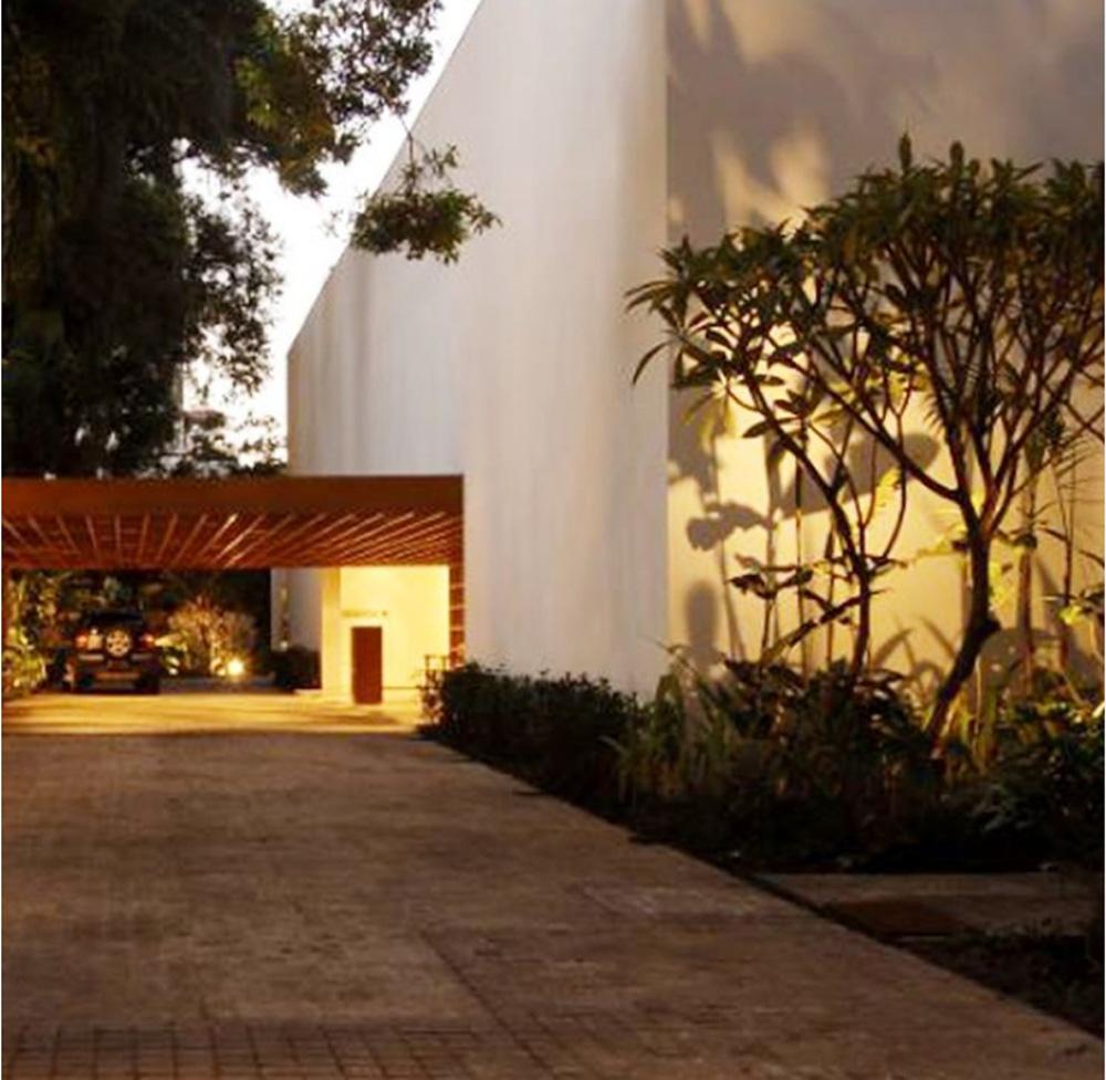 Foto de um grande galpão pintado de branco com entrada e porta iluminada. Algumas árvores ao lado