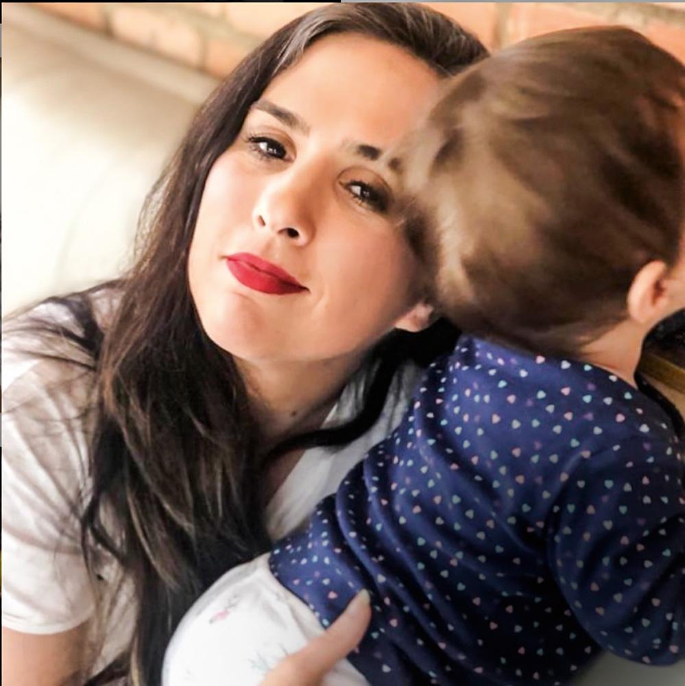 A imagem mostra Tata Werneck segurando seu filho, que está de costas para a câmera, no colo. Ele é um bebê.