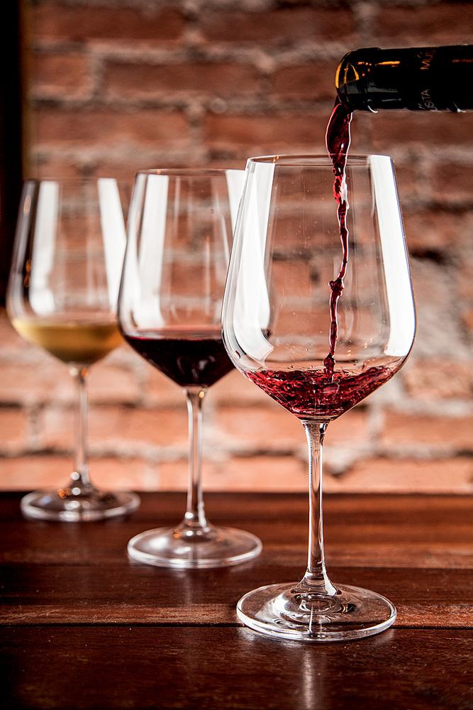 Três taças de vinho alinhadas em diagonal sobre mesa de madeira. Ao fundo com vinho branco, no meio com tinto e na ponta com tinto sendo servido.
