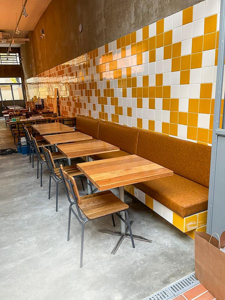 Ambiente do De*Segunda decorado por parede de azulejos brancos e amarelos