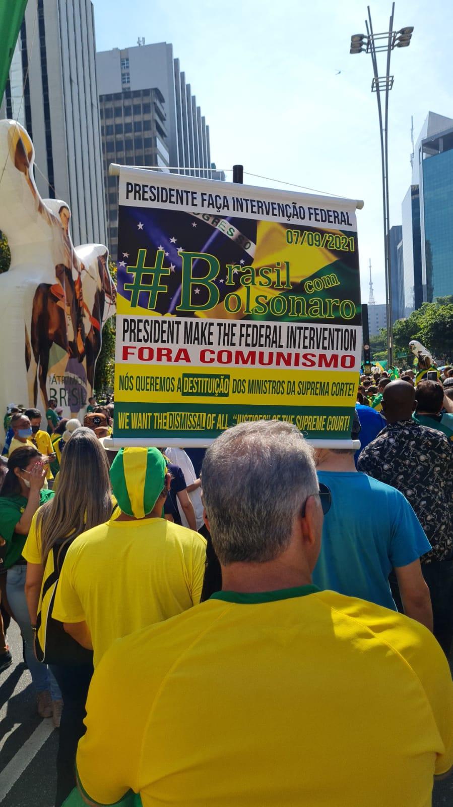 Imagem mostra multidão e cartaz que diz: presidente faça intervenção federal