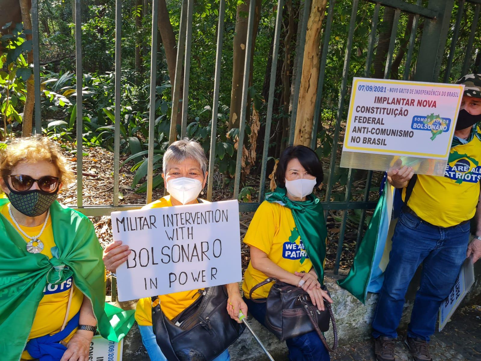 Imagem mostra três senhoras, uma dela segura um cartaz que diz: militar intervention with bolsonaro in power