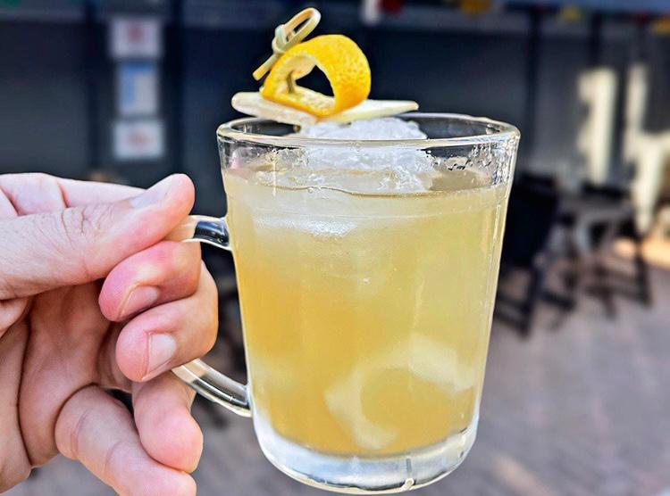 Caneca de vidro serve drinque de cor amarela com gelo e detalhe decorativo de casca de laranja