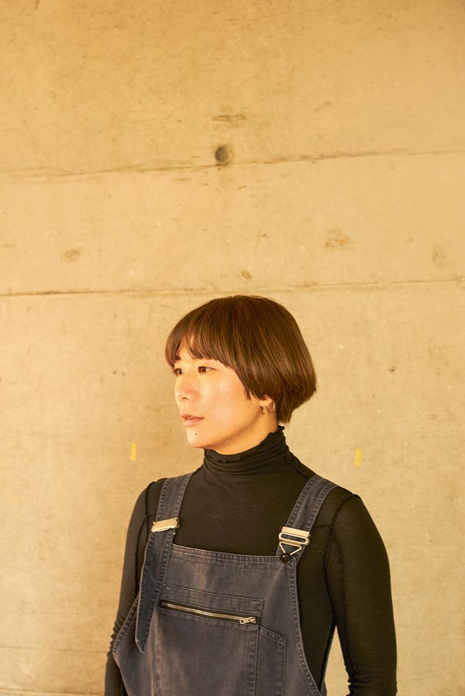 yuko mohri fotografada contra uma parede de perfil